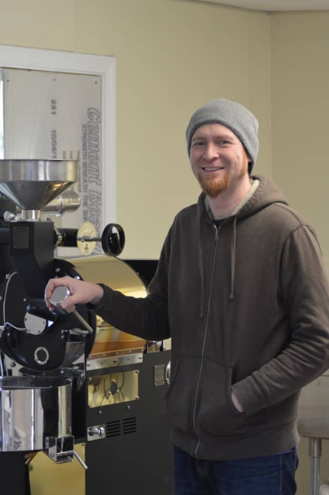 Sherman resident John Rich, owner of Sacred Grounds Coffee Roasters, poses in front of his coffee roaster Monday.