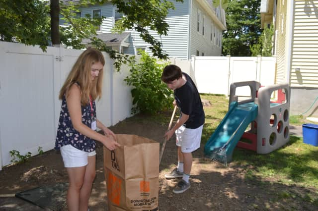 Jessica Power, of Torrington, and Nick Loris, of Fairfield, help clean the backyard at Caroline House in Bridgeport, as part of The SHU Journey summer program.