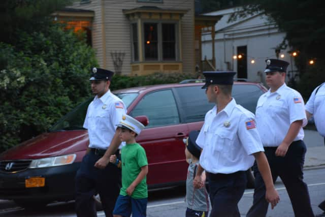 Harrison firefighters, with kids by their sides, marched in the Mount Kisco Fire Department's parade in July. Fundraising accounts at the downtown Harrison Fire Department are being examined by the Westchester County District Attorney.