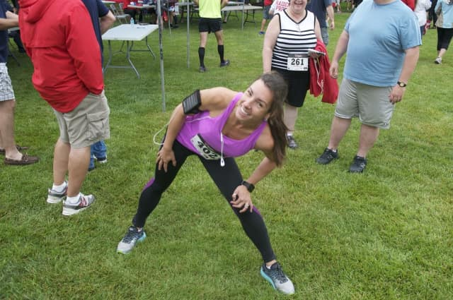 A runner stretches prior to a 5K.