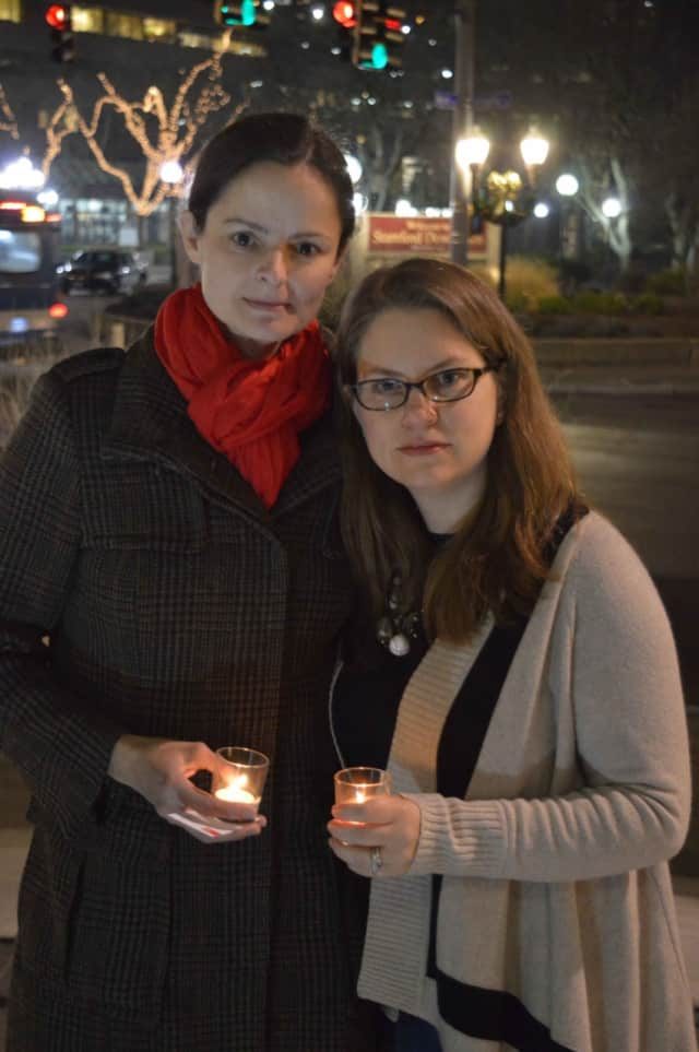 Wendy Skratt and a fellow member of the ENOUGH Campaign gather at a vigil for gun violence Thursday evening in Stamford.