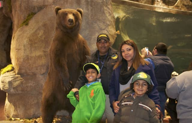 A family poses with a bear at the new Bass Pro Shop at the grand opening in Bridgeport on Wednesday.