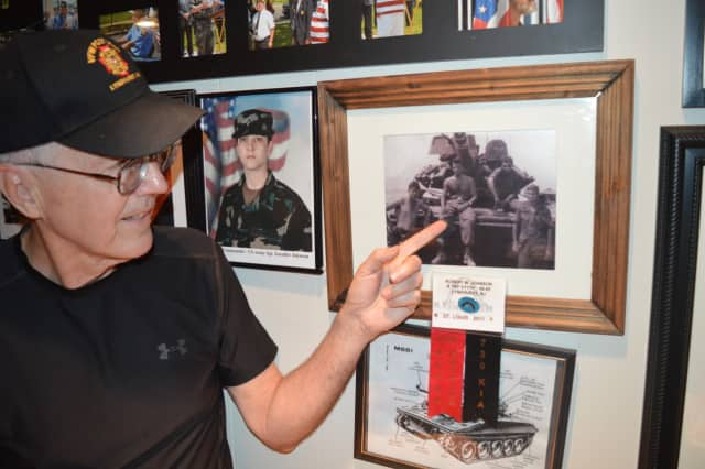 "Thomas Graffam points to a picture of Robert ""Wayne"" Johnson on the wall of the VFW hall"