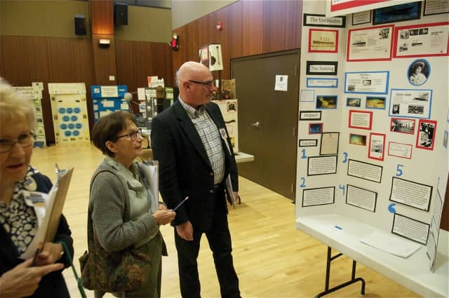 Judges view history projects Saturday at Sacred Heart University.