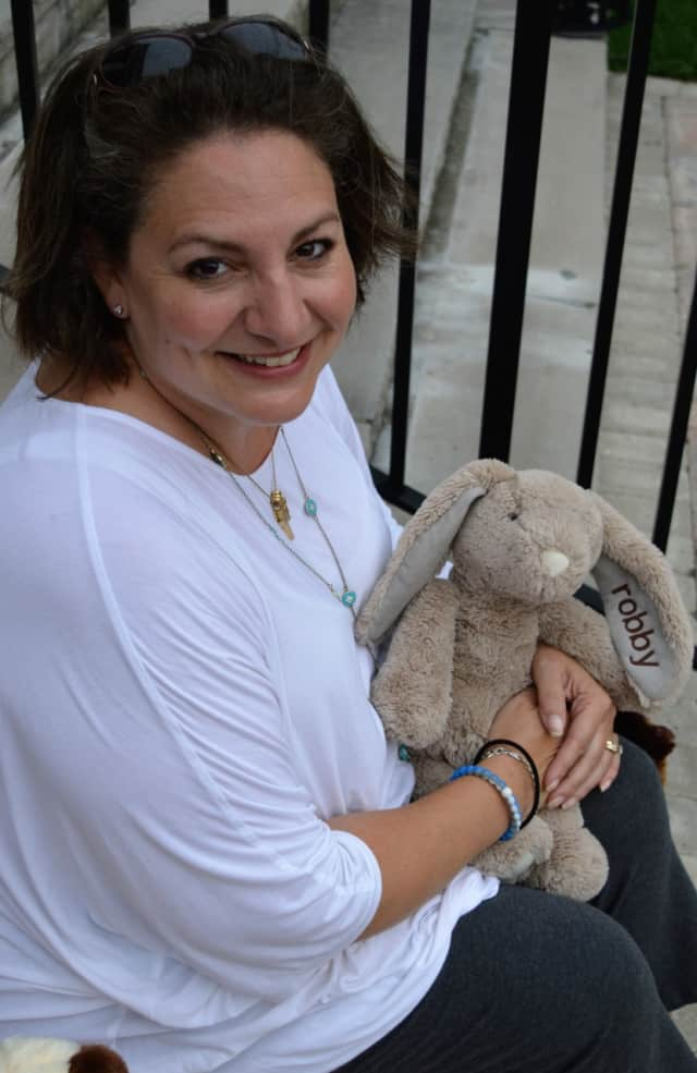 Lisa Oliveri Vreeland holding a stuffed animal from Robby's Rabbits on the steps of her church, St. Paul's Evangelical Lutheran Church in Closter.