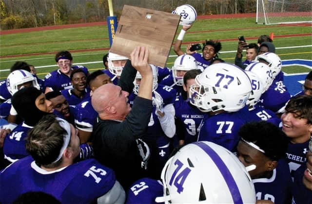 New Rochelle coach Lou DiRienzo hoisting the Section 1 championship trophy with his players.