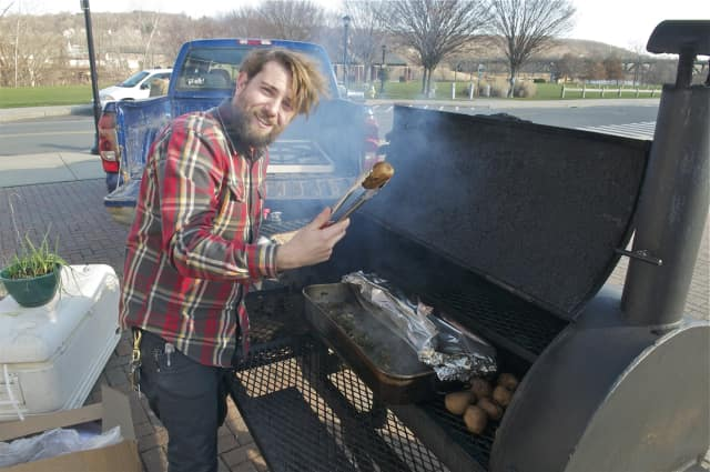 Shelton's Whitehill Smoke Eaters prepares brisket in a smoker outside of the indoor farmers market.