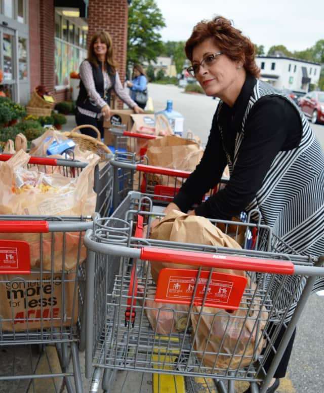 Prominent Properties Real Estate Agents Juliette Gorham, foreground, and Sophia Meneve organize donated groceries outside the Allendale ACME.