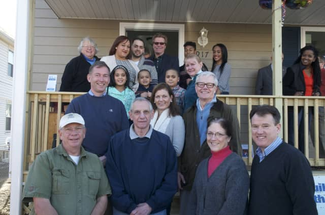 The Soto family stands on the steps of their new home with a group of Habitat volunteers who helped build the house.