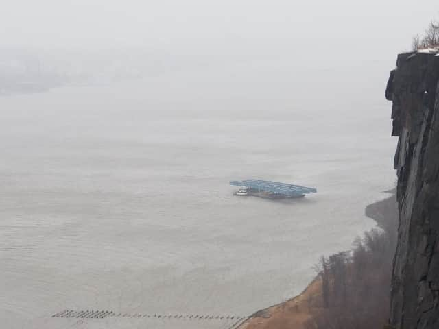 Multiple barges are floating loose on the Hudson River.