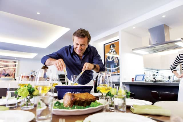 Chef Daniel Boulud preparing to serve a meal to friends at his home. Photograph by Thomas Schauer.