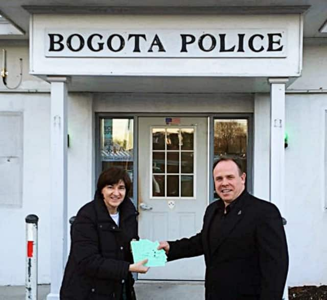 Daniele Fede donates Fix It Up Raffle tickets to the Bogota Police Department's Chief Daniel Maye.