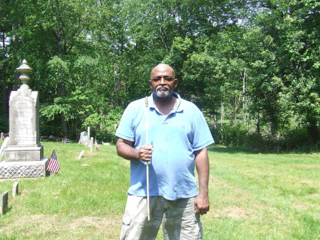 David Thomas holds an empty flag pole at the African American cemetery at Greenwood Union Cemetery in Rye where American flags were ripped from their poles, the apparent work of vandals.
