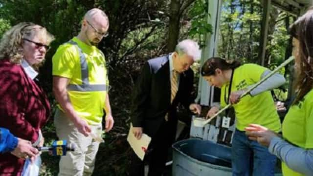 Rockland County Executive Ed Day, center, and others examine potential breeding places for mosquitoes while touring an abandoned home in Chestnut Ridge recently.