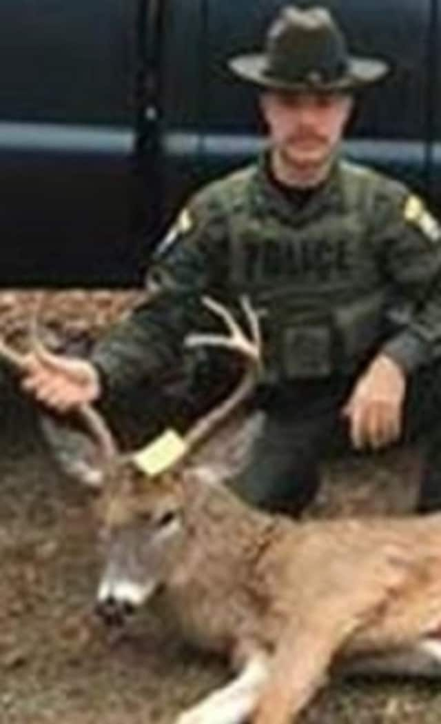 State Environmental Control Officer Anthony Drahms with a buck that the DEC says was illegally taken in Putnam County. The hunter, who was charged with violating state law, told the officer that he did it for his kid, the DEC says.