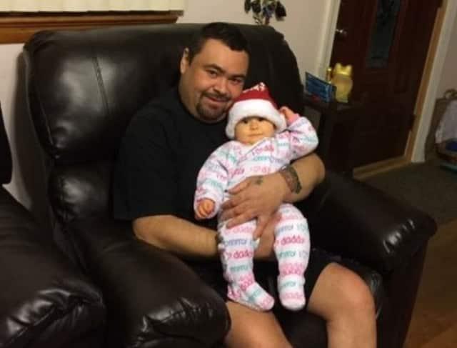 Dennis Maldonado holds his daughter, Isabella.