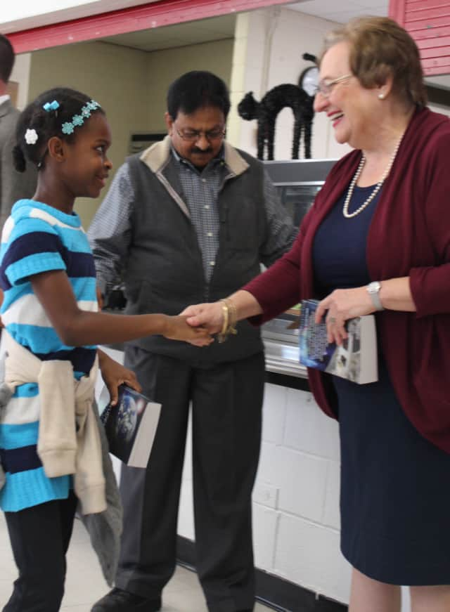 Rotarians Barbara Eannazzo and Syed Alirahi, speaking with a third-grader, presented dictionaries to each student during their visit to Alice E. Grady Elementary School.