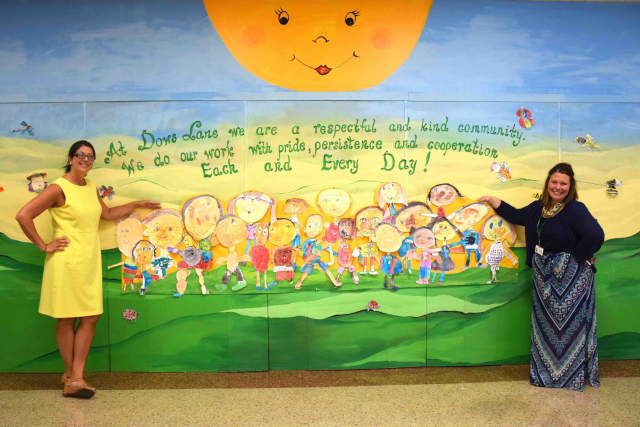 (from left) Dows Lane Elementary School Principal Deborah Mariniello and Assistant Principal Jacquelyn Salcito stand by the school's mural.
