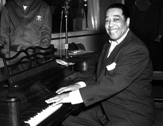 Duke Ellington, famous jazz musician, poses with his piano at the KFG Radio Studio, in 1954.