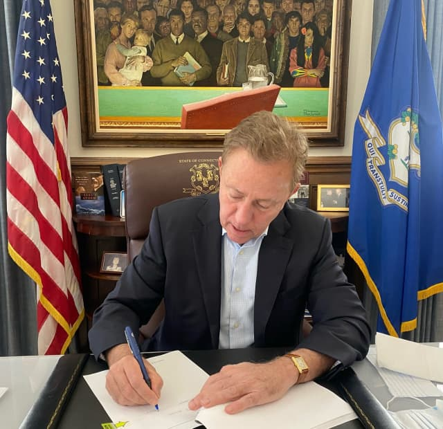 Connecticut Gov. Ned Lamont signing the bill into law.