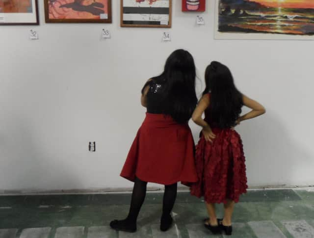 Two girls contemplate art work on display.