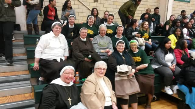 The Felician Sisters show their support for the Felician University basketball teams with both cheers and prayers.