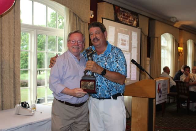 Michael O'Connor of Coldwell Banker Residential Brokerage's Yorktown Heights office presents a trophy to Rich McNichol of McNichol Home Inspections. McNichol's foursome won the annual charity tournament.