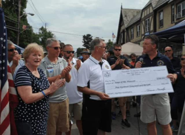 Sen. Terrence Murphy, R-Yorktown, presents Mount Pleasant Supervisor Carl Fulgenzi with a check for $500,000 in Hawthorne. The state grant will be used to improve the town's business district in Hawthorne.