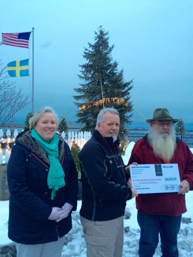 Black Rock Food Pantry leaders Sheila Dunn and Bernie Lee accept a large donation from Norden Club President Ray Corby.