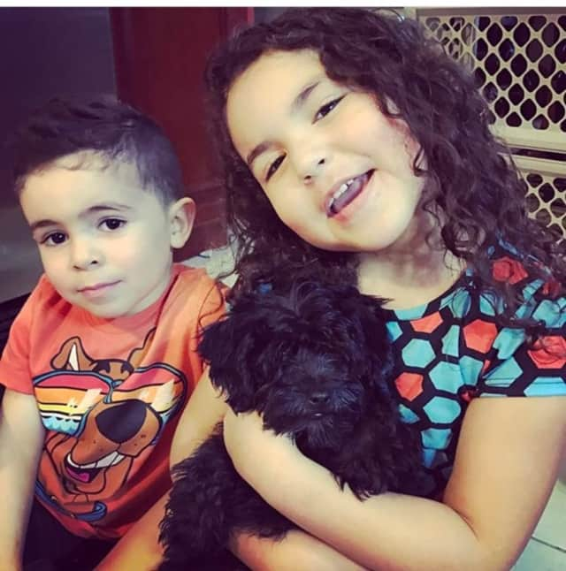 Khloe and Damien Cristostomo with their baby Morkie, who their family rescued after he was surrendered from the Just Pups case.