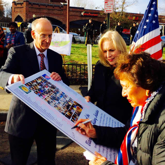 U.S. Rep. Nita Lowey signs a poster last fall at the site of Greenburgh's new Veterans Park, now being built in Hartsdale. Supervisor Paul Feiner hold the sign steady as U.S. Sen. Kirsten Gillibrand looks on.