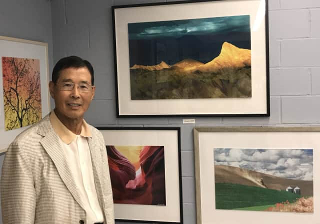 Daniel Lee stands in front of some of his photographs at the Totowa Public Library.