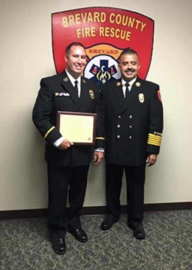 Former New City firefighter Scott Gardiner, left, stands with Fire Chief Mark Schollmeyer after receiving a promotion to district chief in Brevard County, Fla.