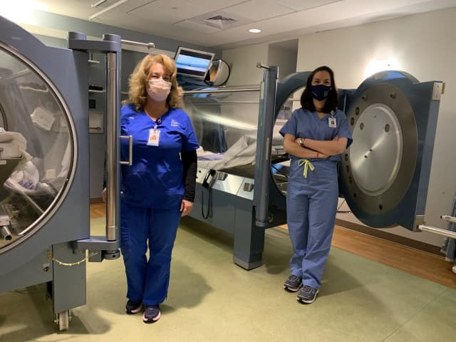 Greenwich Hospital is treating COVID-19 patients with hyperbaric oxygen therapy administered by Ellen Stacom, RN, (left) and Dr. Sandra Wainwright.