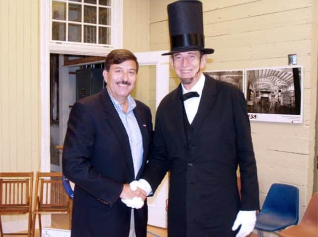 Former mayor and history buff John Testa, left, shakes hands with former teacher, Michael E. Griest, at the Lincoln Depot Museum in Peekskill. Griest, who frequently portrayed Abe Lincoln during city events, died Tuesday at the age of 77.