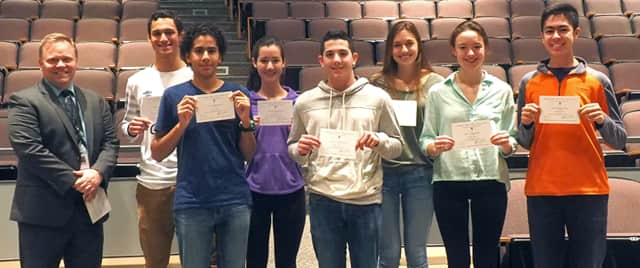 Dillon Bogart, Andrew Carton, Ella Eisinger, Amr El-Azizi, Phillip Milana, Sarah Ryan and Mihoko Sakanaka with their letters of recommendation. Allison Karantzsis, another recipient is not in the picture. Principal Steven Siciliano is at left.