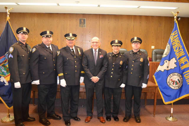 The four members of the Harrison Police Department earning promotions with Mayor Ronald Belmont and Chief Joseph J. Yasinski.