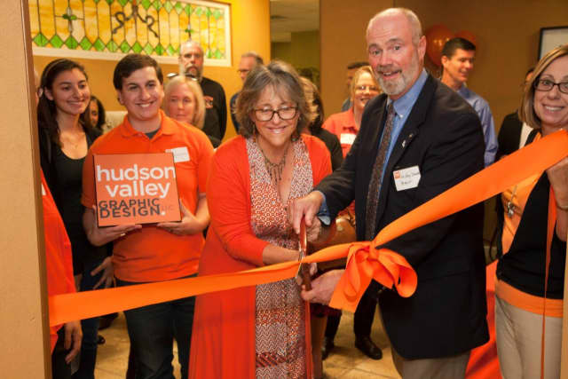 Croton-on-Hudson Mayor Greg Schmidt assists Hudson Valley Graphic Design owner Janeen Violante with the official ribbon cutting ceremony.