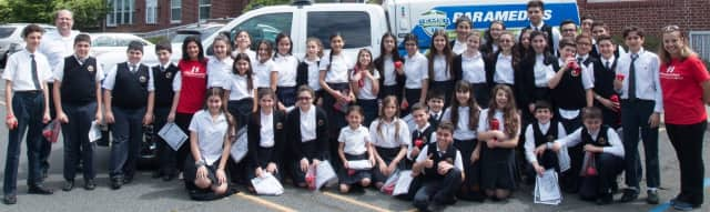 Fifth- through eighth-graders stand in front of the Hovnanian School with members of the Heart and Vascular Hospital team at HackensackUMC.