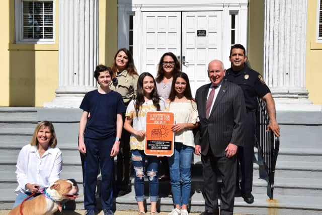 Julie Loparo, left, poses with Brandon Malin, Jordi Katz, Ali Green and First Selectmen Jim Marpe. In the back row are Animal Control Office Gina Gambino and Carla Eicher and Deputy Police Chief Vincent Penna.