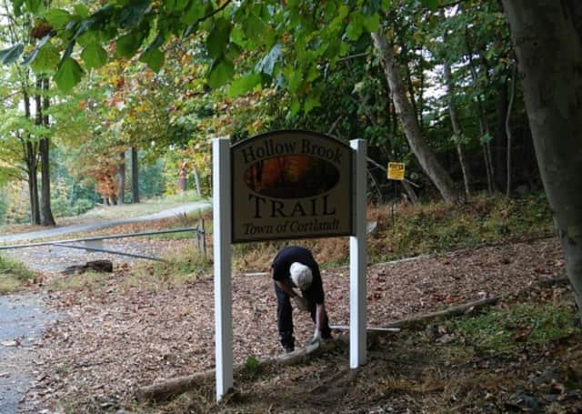 A worker installs the sign marking the beginning of the town of Cortlandt's brand-new Hollow Brook Trail. It will be officially opened at 4:30 p.m. on Thursday, Oct. 20.