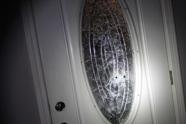 Damage to the home's front door during a drive-by shooting.