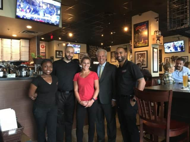 Englewood Mayor Frank Huttle and employees of the newly opened Anthony's Coal Fired Pizza