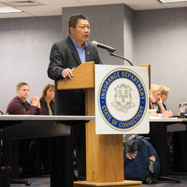 State Sen. Tony Hwang (at podium) addresses state insurance regulators during an Aug. 3 public hearing in Hartford on proposed double-digit health insurance rate hikes. It's not too late for citizens to submit their concerns about the rate increases.