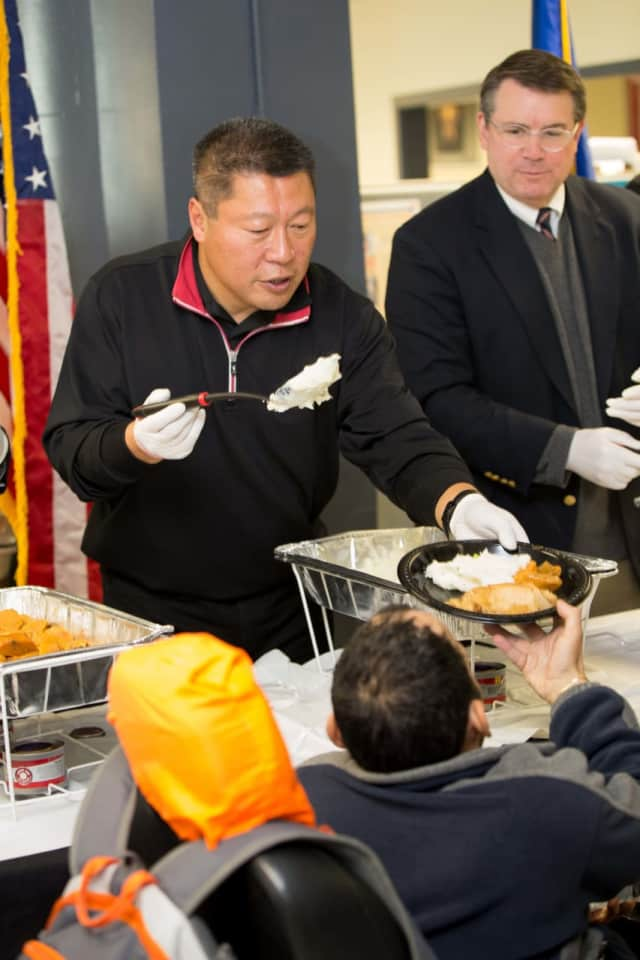 State Sen. Tony Hwang helps serve the annual Thanksgiving dinner at the Bridgeport American Jobs Center.