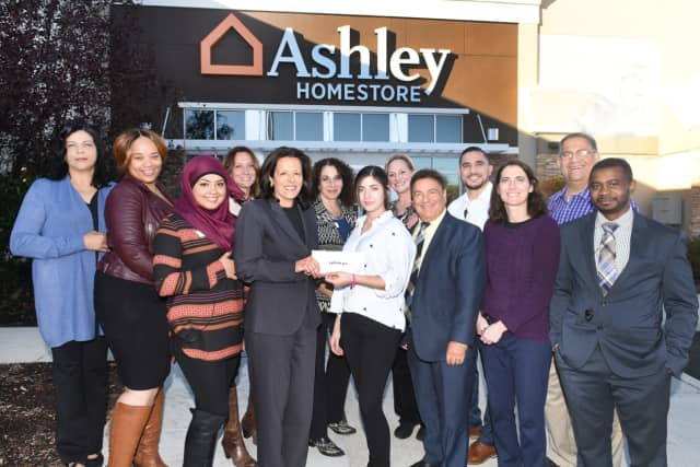 The employees of Ashley Furniture present a check to Sandy Carapezza, director of development at The Valley Hospital Foundation.