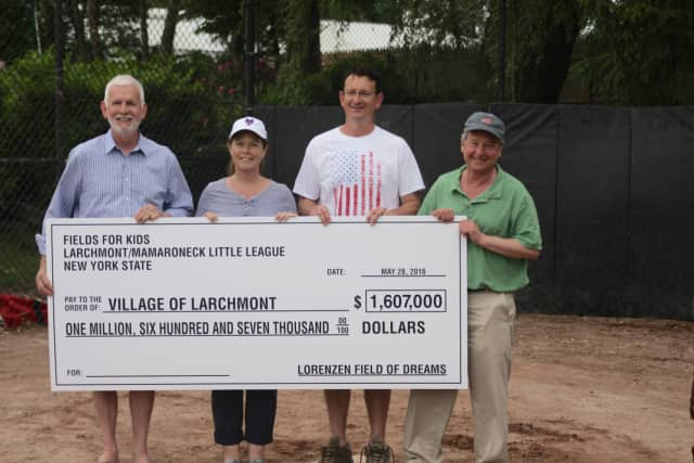 Jim Hanley, president of Fields for Kids, Bill Nachtigal, president of Larchmont Mamaroneck Little League, and state Assemblyman Steve Otis present a check for $1.6 million to Larchmont Mayor Lorraine Walsh.