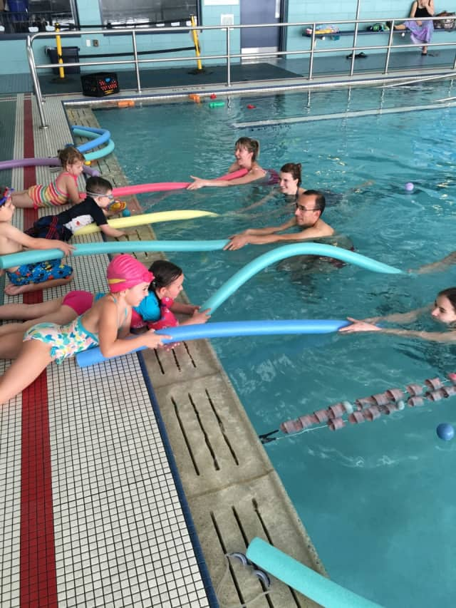 "Children learn a safe procedure for helping a ""struggling"" swimmer, played by mom or dad at the Wyckoff Family Y."