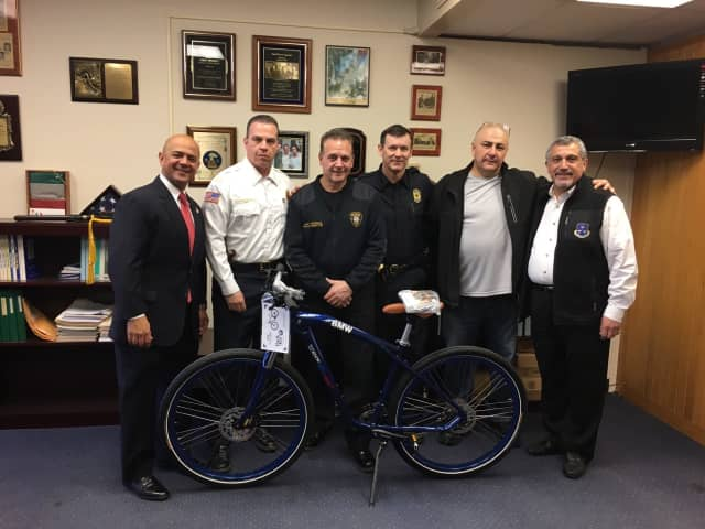 BMW officials and the Paterson Police Department with its new bicycle.