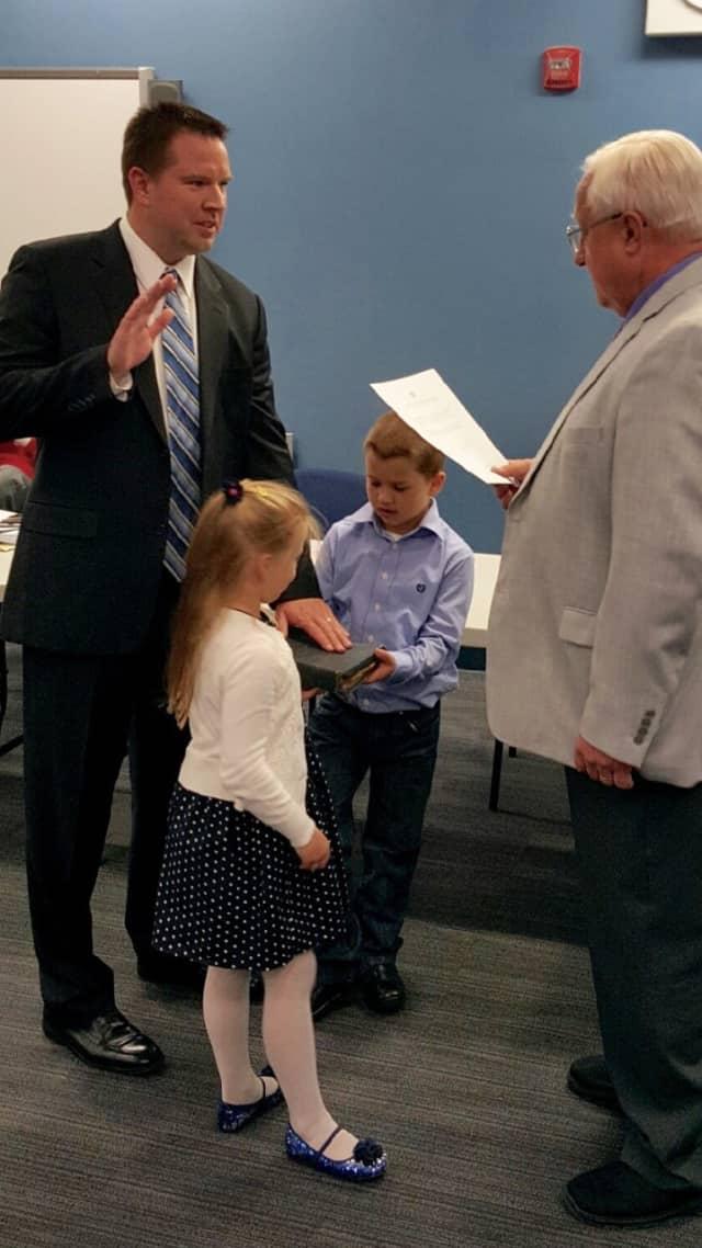 Board Secretary Joe Brunacki swears in Thomas Brynczka with his children Jacob and Aleksandra by his side.